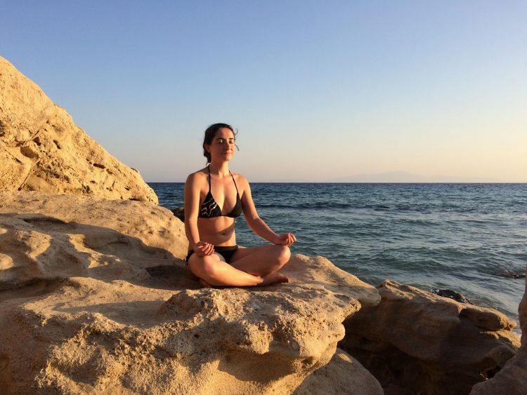 Iva Says sitting on a rock by the sea
