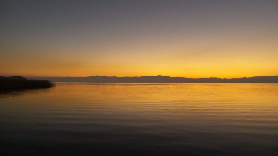 Watching the sunset over Lake Ohrid. Beautiful sunset photos. Amazing sunset photos. Sun is setting over the horizon. Beautiful red and orange colors over the mountains as the sun sets.