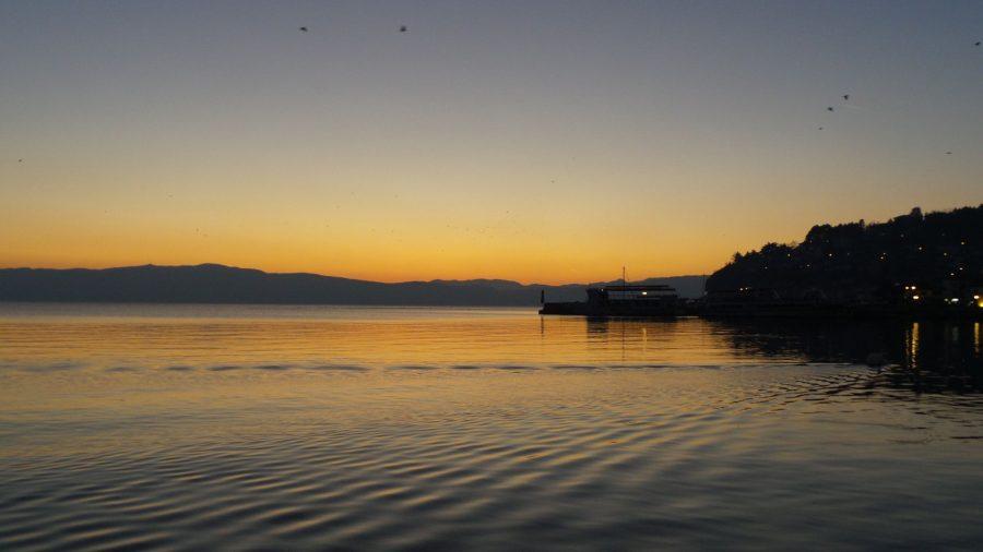 Orange sunset setting over the horizon at Lake Ohrid. Watching the sunset over Lake Ohrid. Beautiful sunset photos. Amazing sunset photos.
