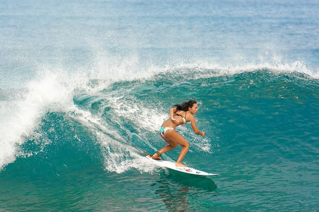 A woman on a surfboard surfing in the ocean. The water travel element. Be a master of the waves.