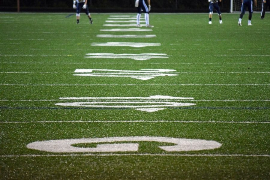 Up close look of the yard lines in an American football field with football players in the back.