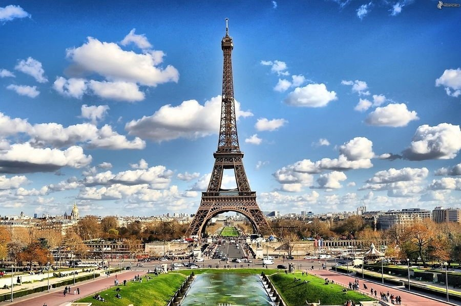 The Eiffel Tower in Paris, France with clouds in the sky behind the tower.