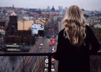 A woman on a balcony overlooking a city in the distance.