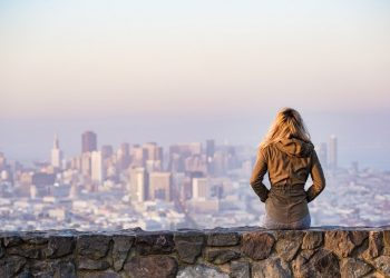 """A woman resting on a small rock wall overlooking to a city in the distance. Feature image for the blog post """"Big Buildings, Small Cost: Getting The Most Out Of A City Break"""" on ivasays.com"""