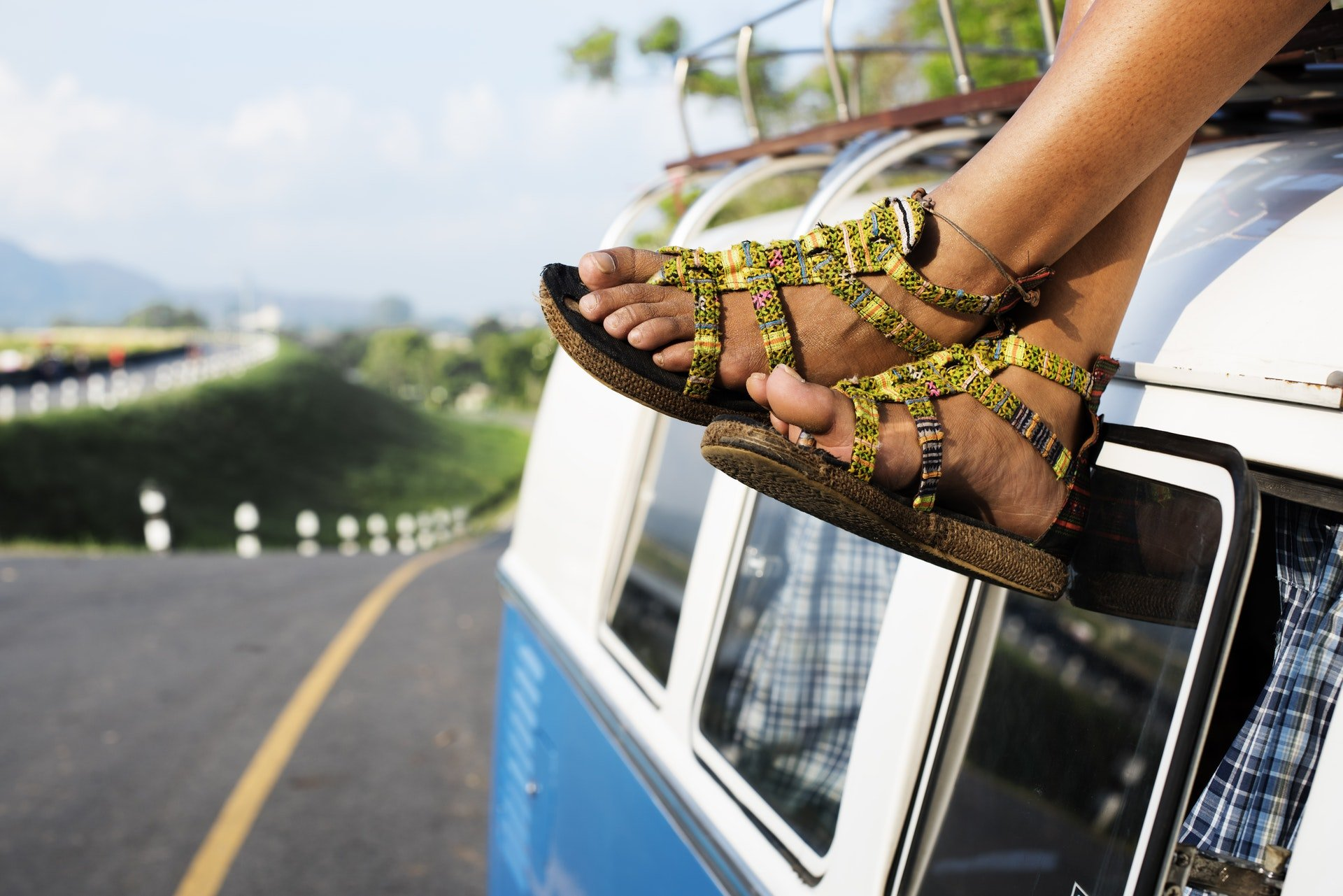 Man's feet dangling from the top of an older RV that is white and blue while on a road trip.