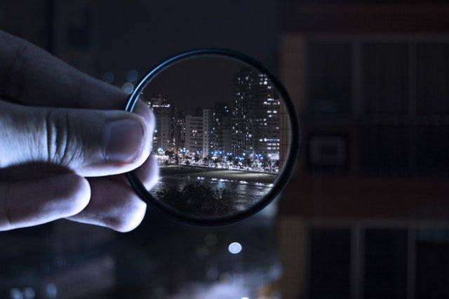 A man's hand holding a magnifying lens that shows a city in crystal-sharp image.