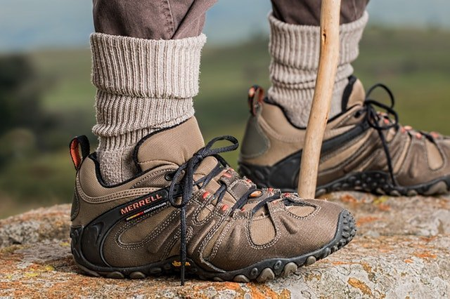Close up shot of Merrell brown hiking boots worn by a man with grey, brown socks and a hiking wooden stick between the legs. What are your favorite hiking boots? Great way to save space in your bag when going hiking abroad is to wear your hiking boots on the plane, since they take up a lot of space due to their size.