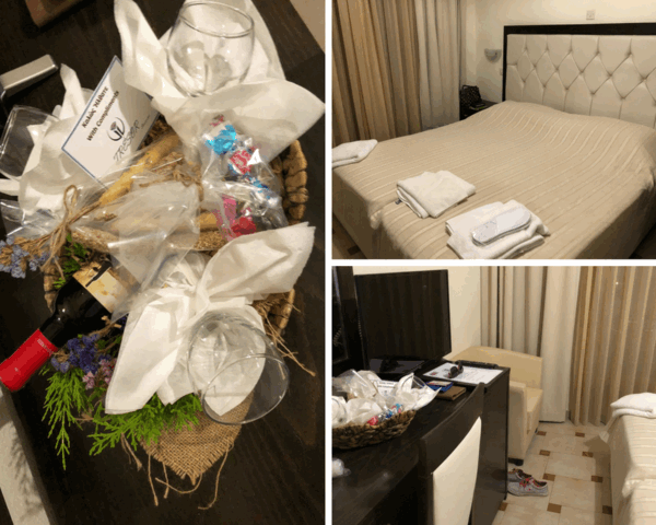 Tresor Sousuras Hotel staff left a welcome package of three wine glasses, red wine bottle by Tresor Sousuras Hotel, and bread sticks as snacks. The queen bed in Tresor Sousuras Hotel was neatly made and the welcome package was right next to the TV on the table in front of the bed.