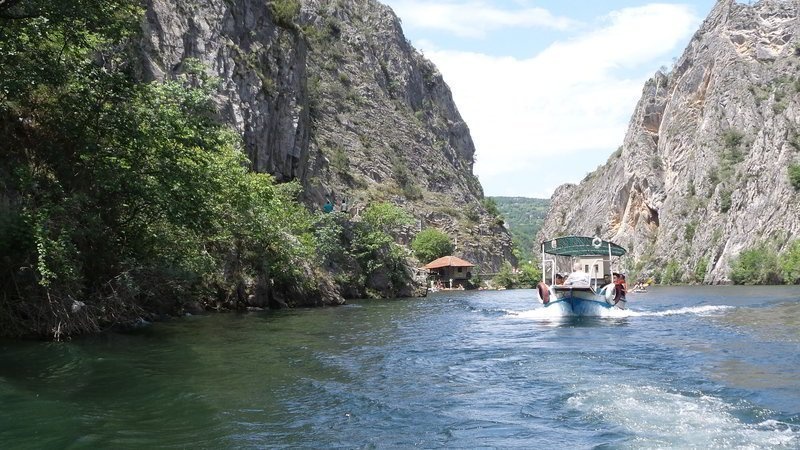 A small tourist boat with visitors on the way to cave Vrelo.
