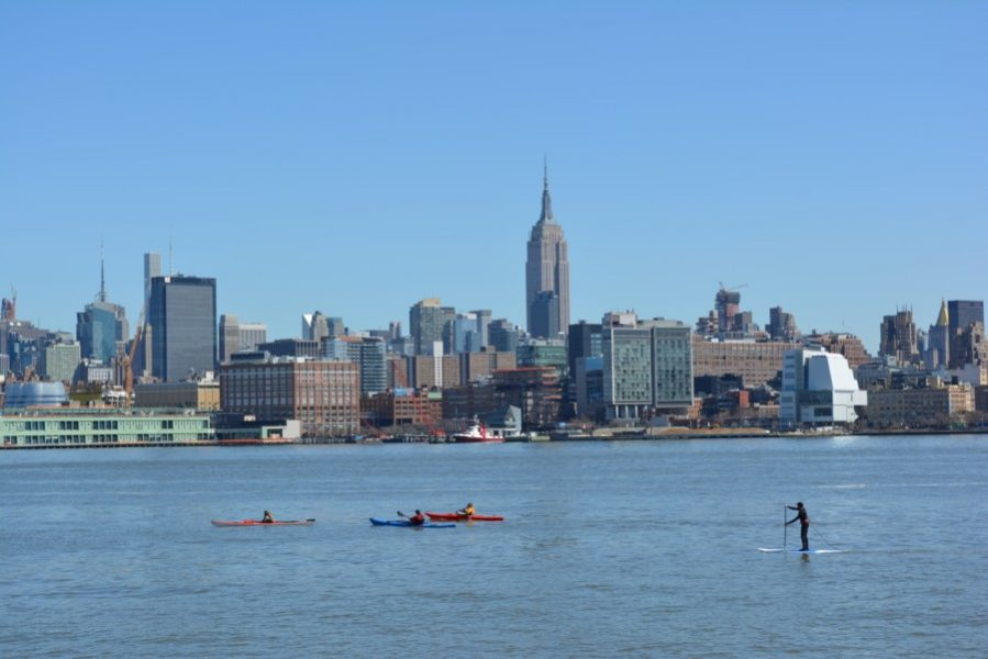 View to Manhattan and the Empire State building from Hoboken, NJ with kayaks in the Hudson River.