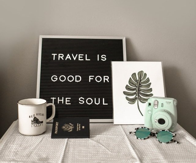 "Black bulletin board with ""Travel is Good for the Soul"" writing. Coffee mug, US passport, picture of a leave, green sunglasses, and a small green Fuji Mini8x camera on a table."