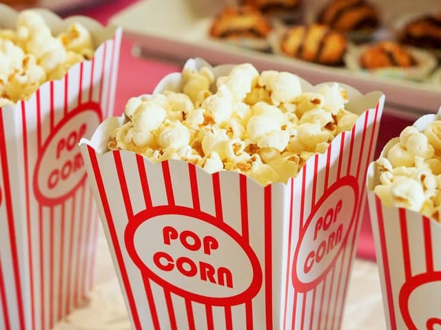 Popcorn popped in a standard white with red stripes popcorn carton for a movie night.