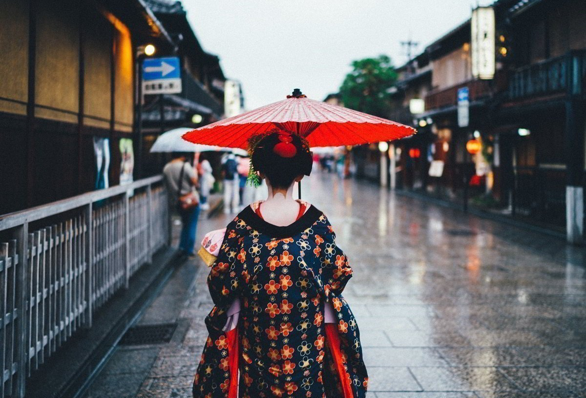 A Japanese woman with a red umbrella on a street in Japan.