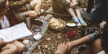 People sitting on the ground with camping gear and food around them in nature.