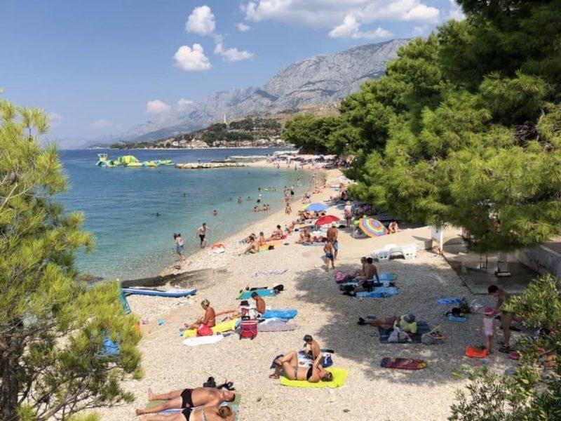 People sunbathing and swimming at the Podgora Beach on the Adriatic Coast in Croatia.