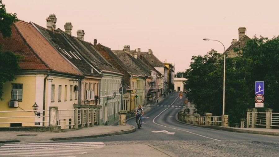 Man on a bicycle riding toward the center of Novi Sad from the Blegrade Gate (Beolgradska Kapija) to Petrovaradin Fortress in Serbia.