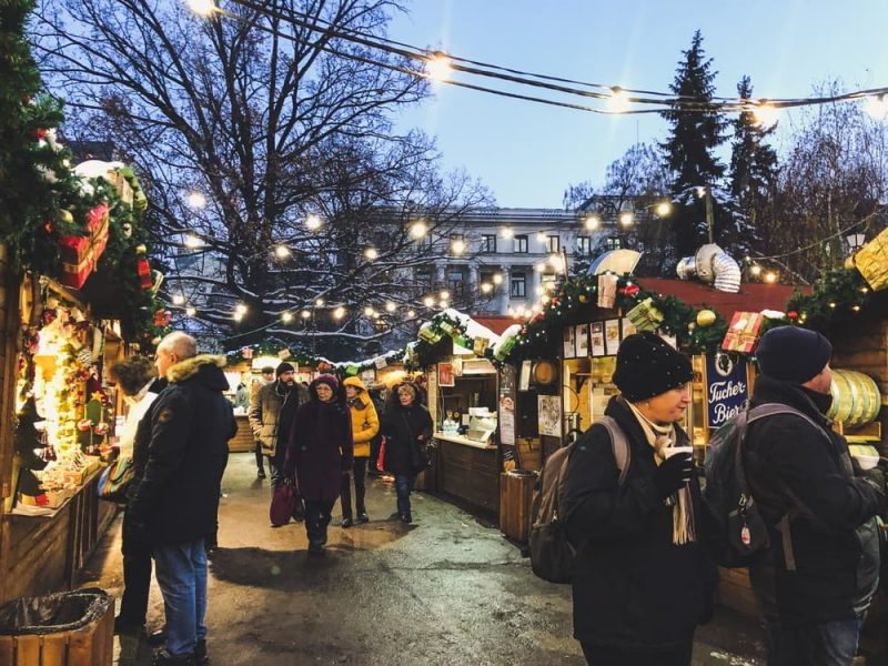 People walking around and drinking at a Christmas market in Sofia, Bulgaria.
