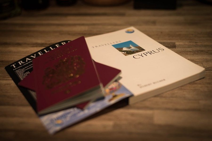 Two red passports over a Cyprus travel guide book.