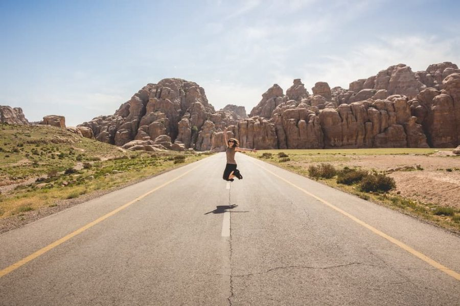 A woman jumping up in the middle of a road with mountains in the background.