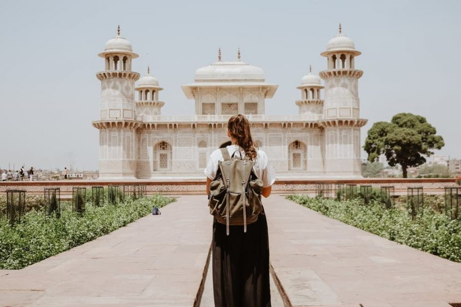 Woman with a backpack standing in front of a temple.