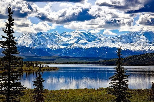 Snow on mountains with a body of water.