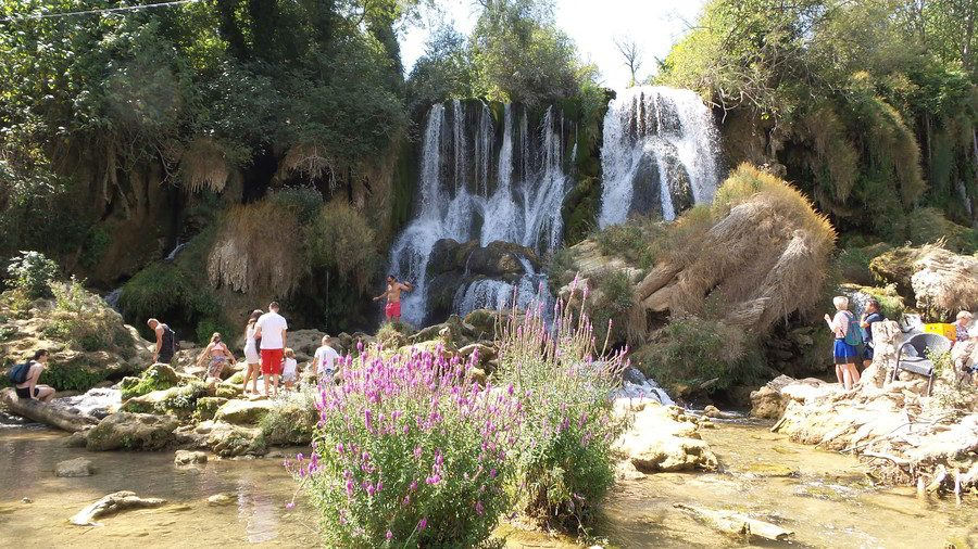 People walking around waterfalls and taking photographs.