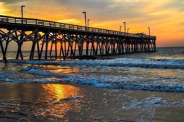 Boardwalk in the ocean during sun down.