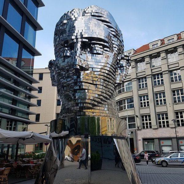 Metal head statue in a city square.