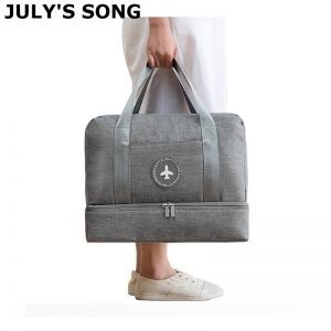 Woman holding grey travel bag.