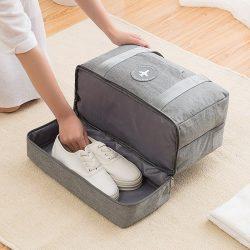 Woman placing shoes in grey travel handbag