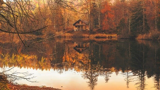 Cottage on a lake with trees during autumn.