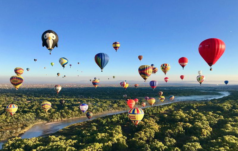 Hot air balloons in air over a valley with a river.