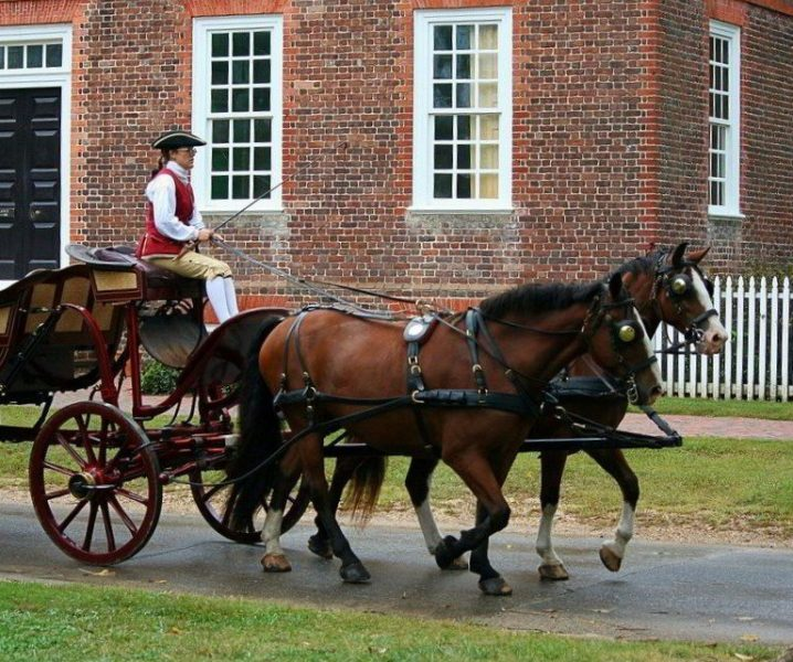 Horse carriage in front of a brick house.