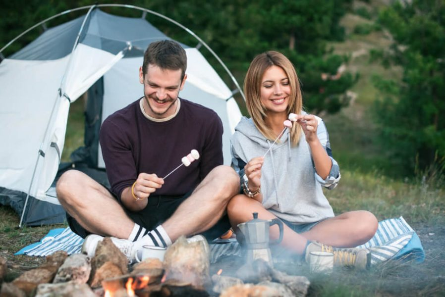 Couple camping outside, fire, smores, camping tent.