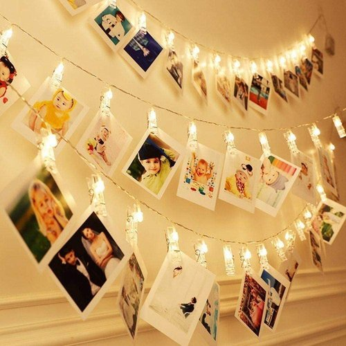 Polaroid photos on wall decorated by LED clips.