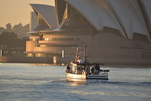 Boat sailing in front of the  Sydney Opera House