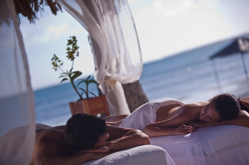 A couple getting a spa massage on the beach at Copamarina Beach Resort & Spa